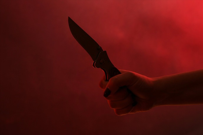 Female hand holding knife on red background_-57881522179979733