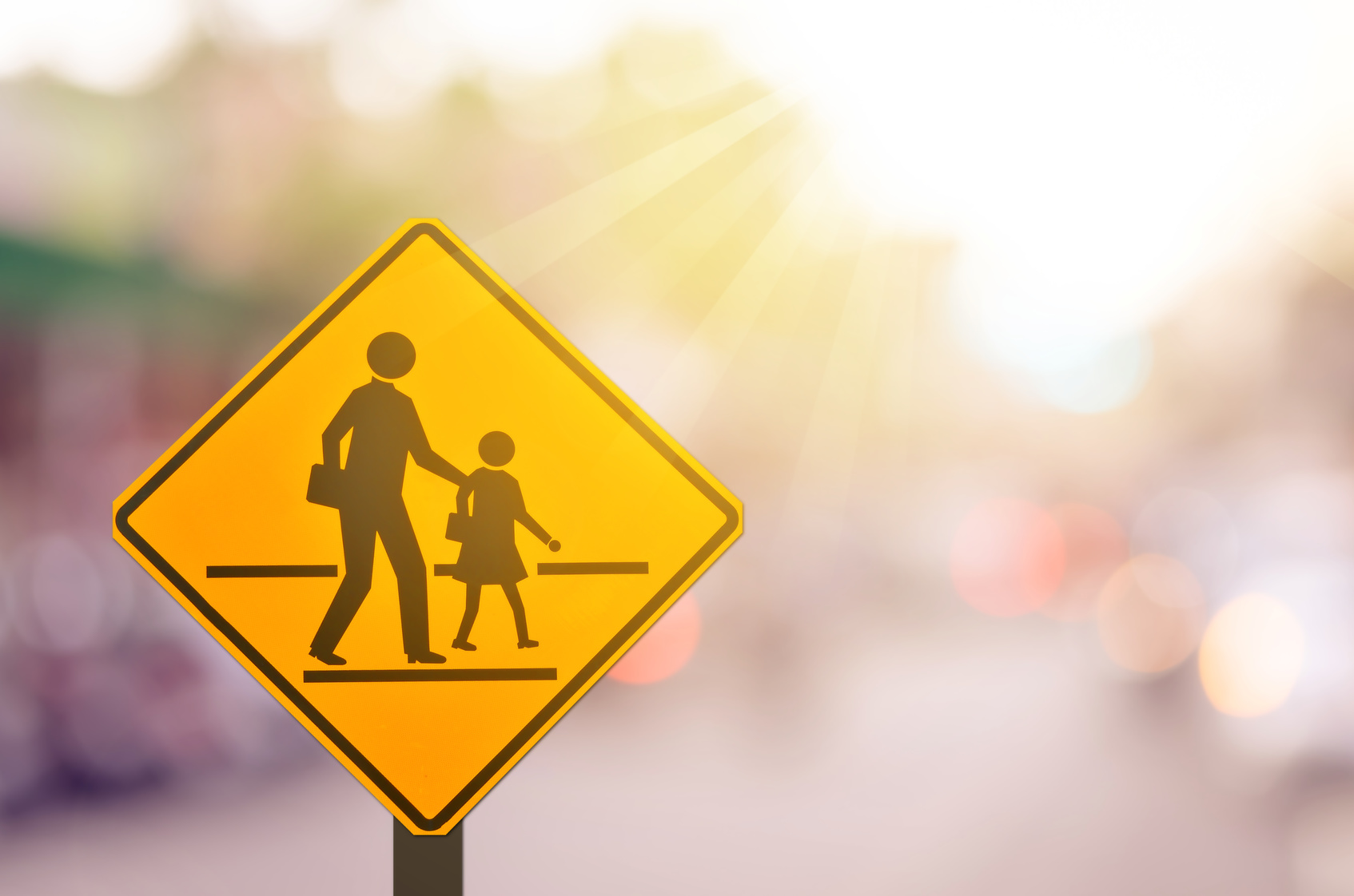 School zone warning sign on blur traffic road with colorful bokeh light abstract background._1507129528627